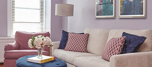 purple guest room with taupe sofa and blue ottoman